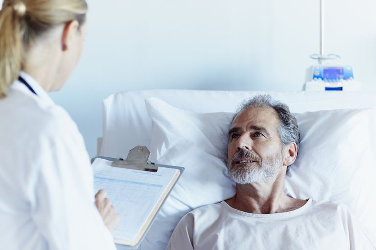man talking to doctor from hospital bed