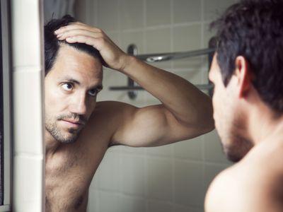 Man looking at hair loss in mirror.
