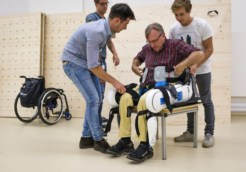 Man with ALS being helped in a chair by other men