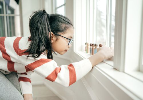 Female child with black hair and glasses lining up figurines on a window sill.