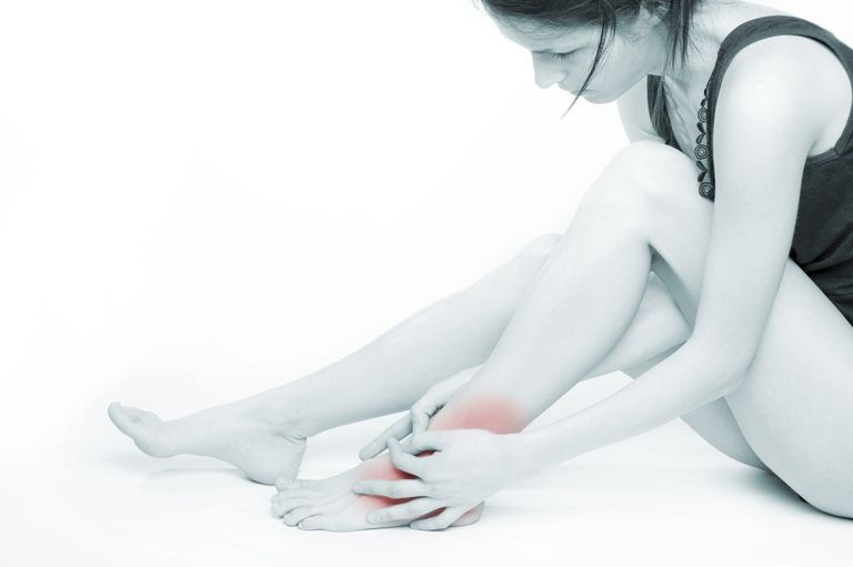 woman holding her ankle, red color showing ankle swelling