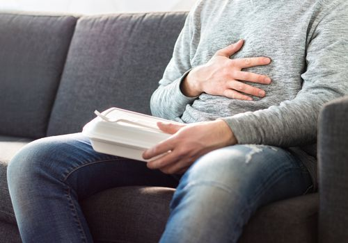 A man sitting on the couch with stomach pain