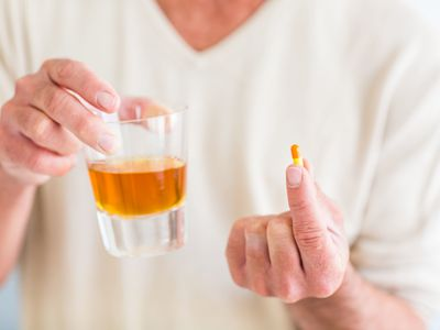 person holding glass of Alcohol and a pill