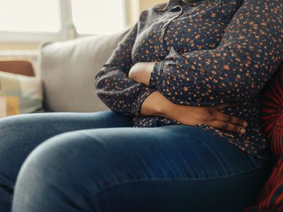 Woman Holding Belly, Feeling Discomfort - Stock Photo