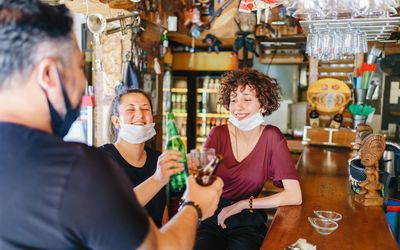 People at a bar with face masks.