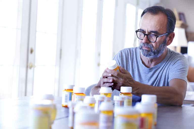 Man Sitting At Table Sorting Through Prescrption Medications