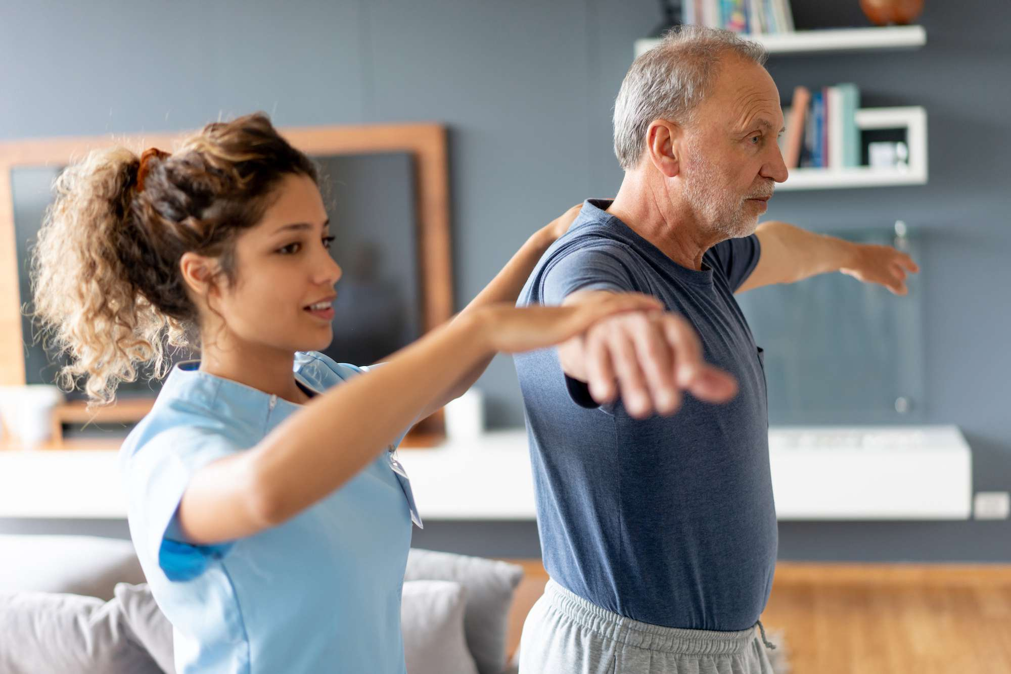 Physical therapist leading older man through shoulder exercise