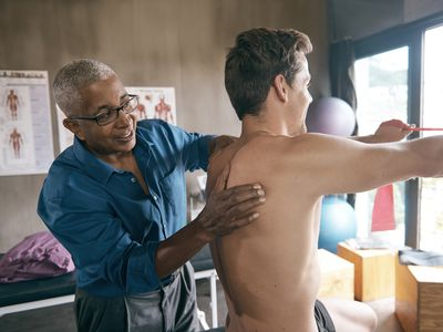 man stretching back and shoulders with physical therapist
