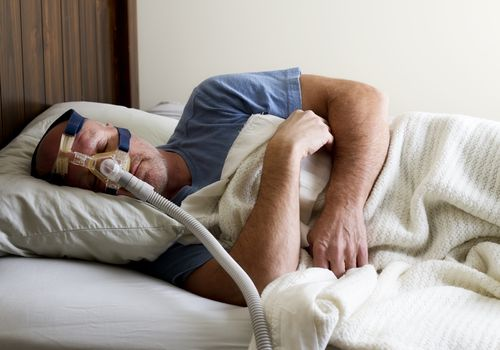 Man Sleeping in bed with sleep apnea mask on