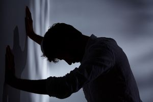A distressed man in silhouette with his hands against a wall.