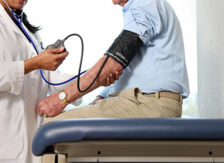Doctor checks man's blood pressure