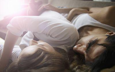 Couple lying on sofa, indoors