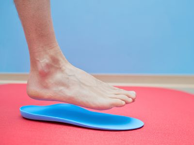 Foot hovering over orthotic shoe insert