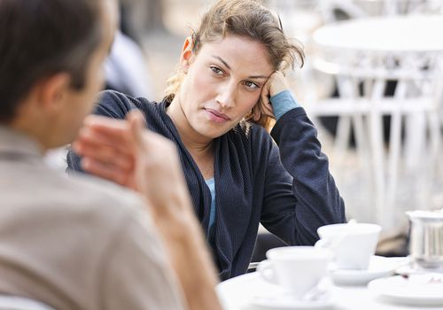 Exasperated woman talking to a man at a cafe