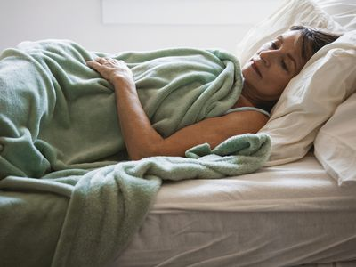 older woman lays in bed with green blanket and stares into space
