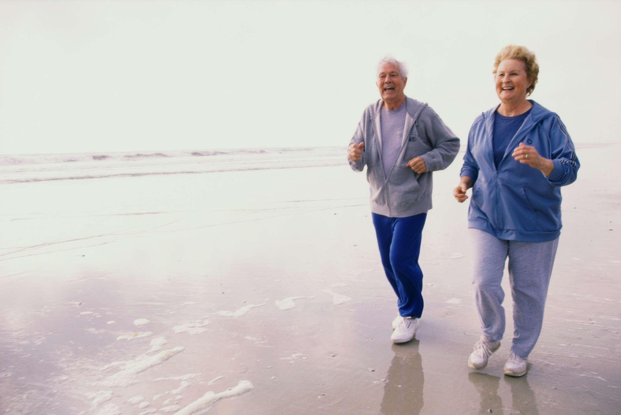 Older adult couple running on the beach