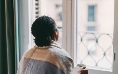 Women in quarantine looking out window with cup of coffee in hand