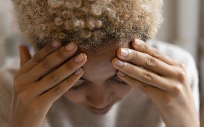 Woman with headache rubbing forehead