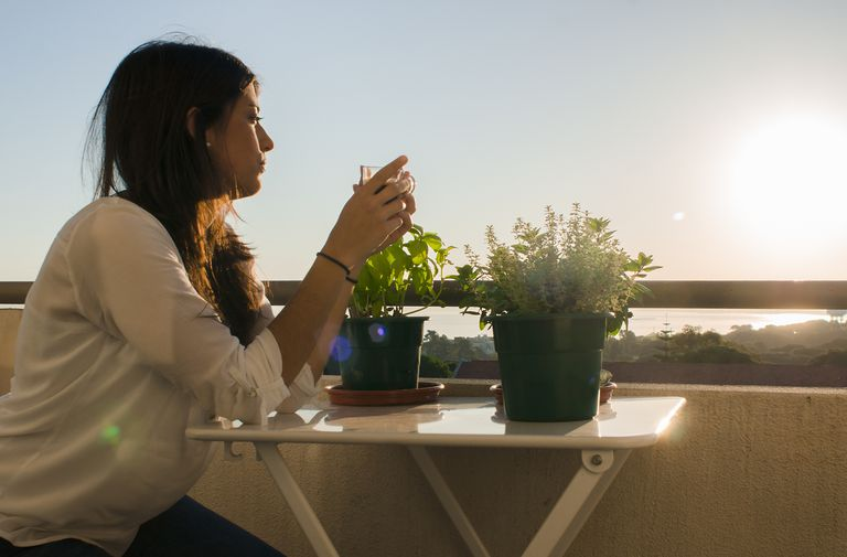 Woman sitting on a patio at sunrise with a cup of coffee