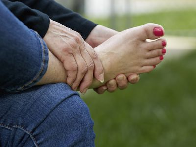 Woman's hand holding her sore foot