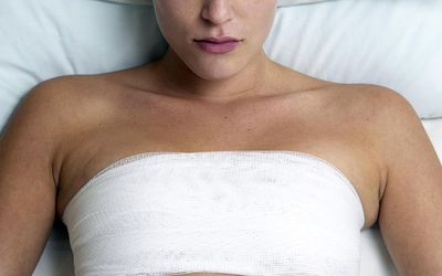Bandaged woman lying in bed