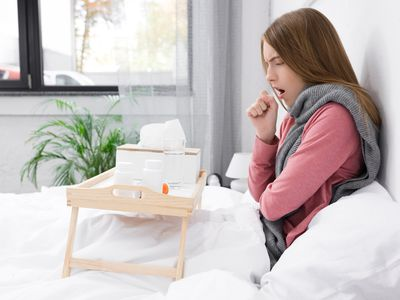 Girl sitting up in bed coughing