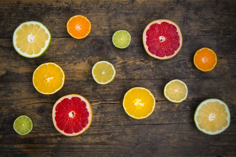 Slices of different citrus fruits on dark wood