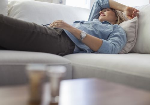 Dizzy woman lying on a sofa