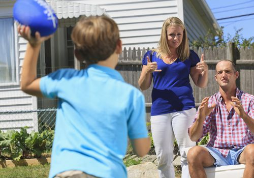 Family with hearing impairments playing football and signing play and pass in American sign language in backyard