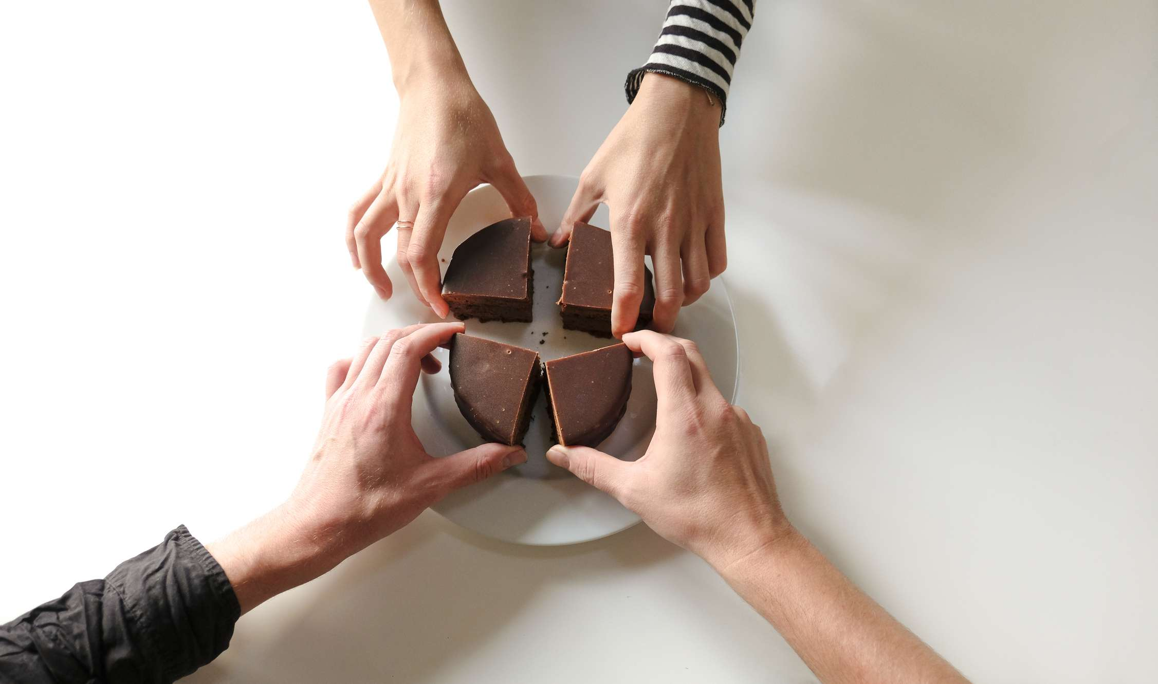 Four people reaching for four pieces of cake