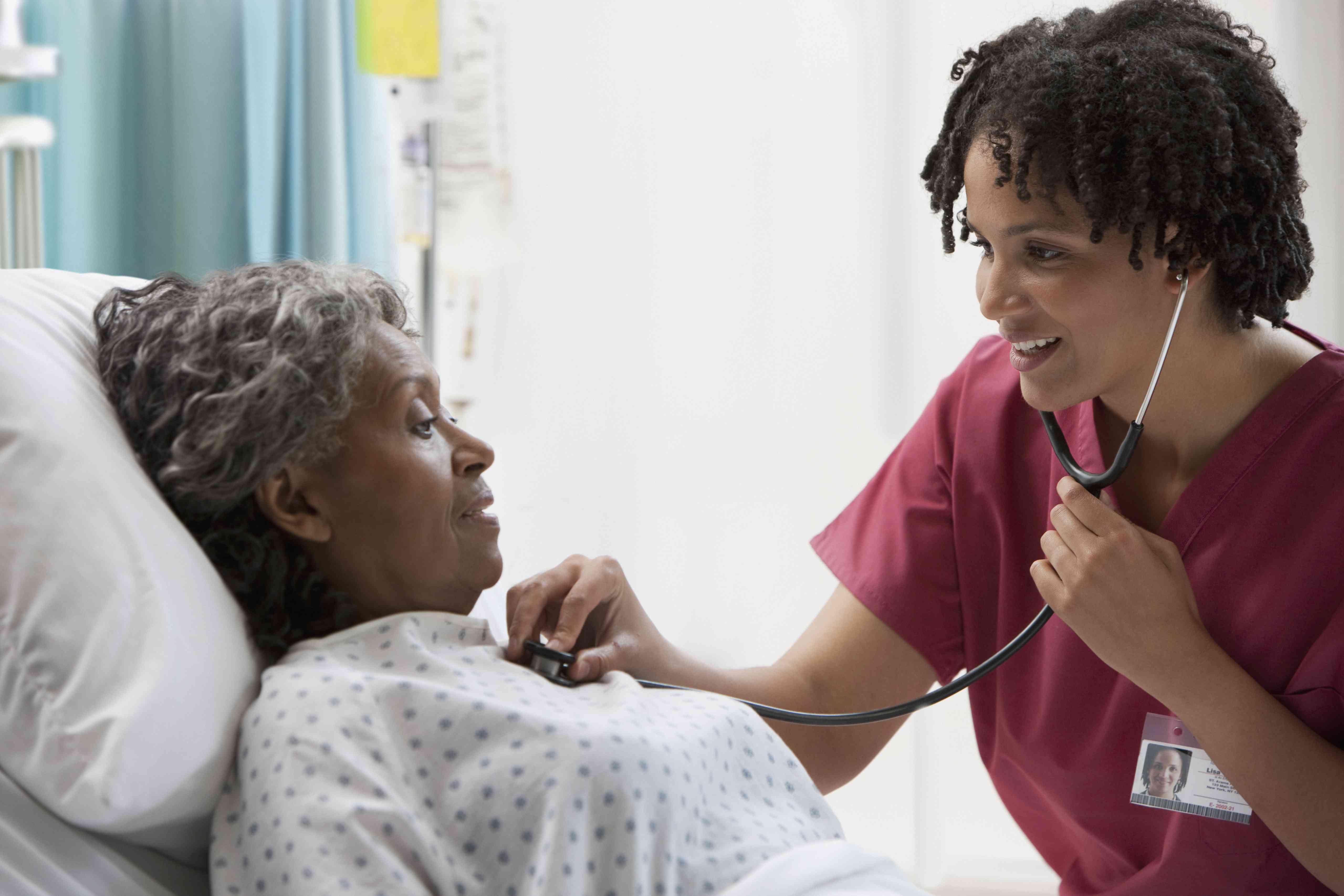 nurse using stethoscope on hospital patient