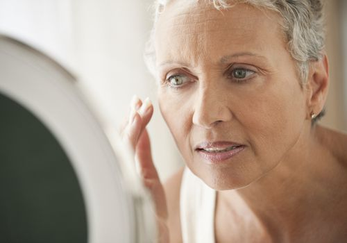 Mature woman applying cream to her face in a mirror