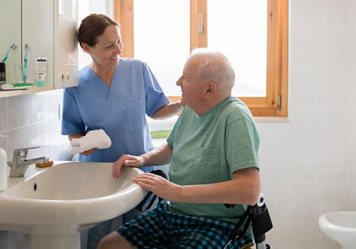 Nurse helping man wash up at a sink