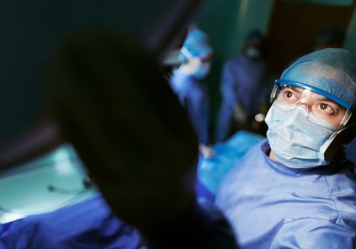 A doctor adjusting light in operating room