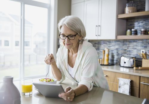 Senior woman wearing glasses and eating fruit while looking at digital tablet in her kitchen
