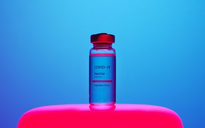 A COVID-19 vaccine ampule on a hot pink stand on a bright electric blue background.
