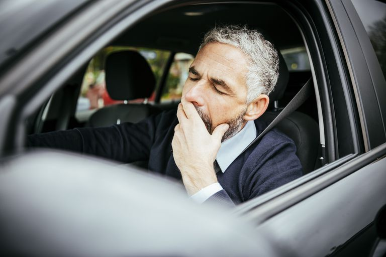 Man falling asleep behind while driving