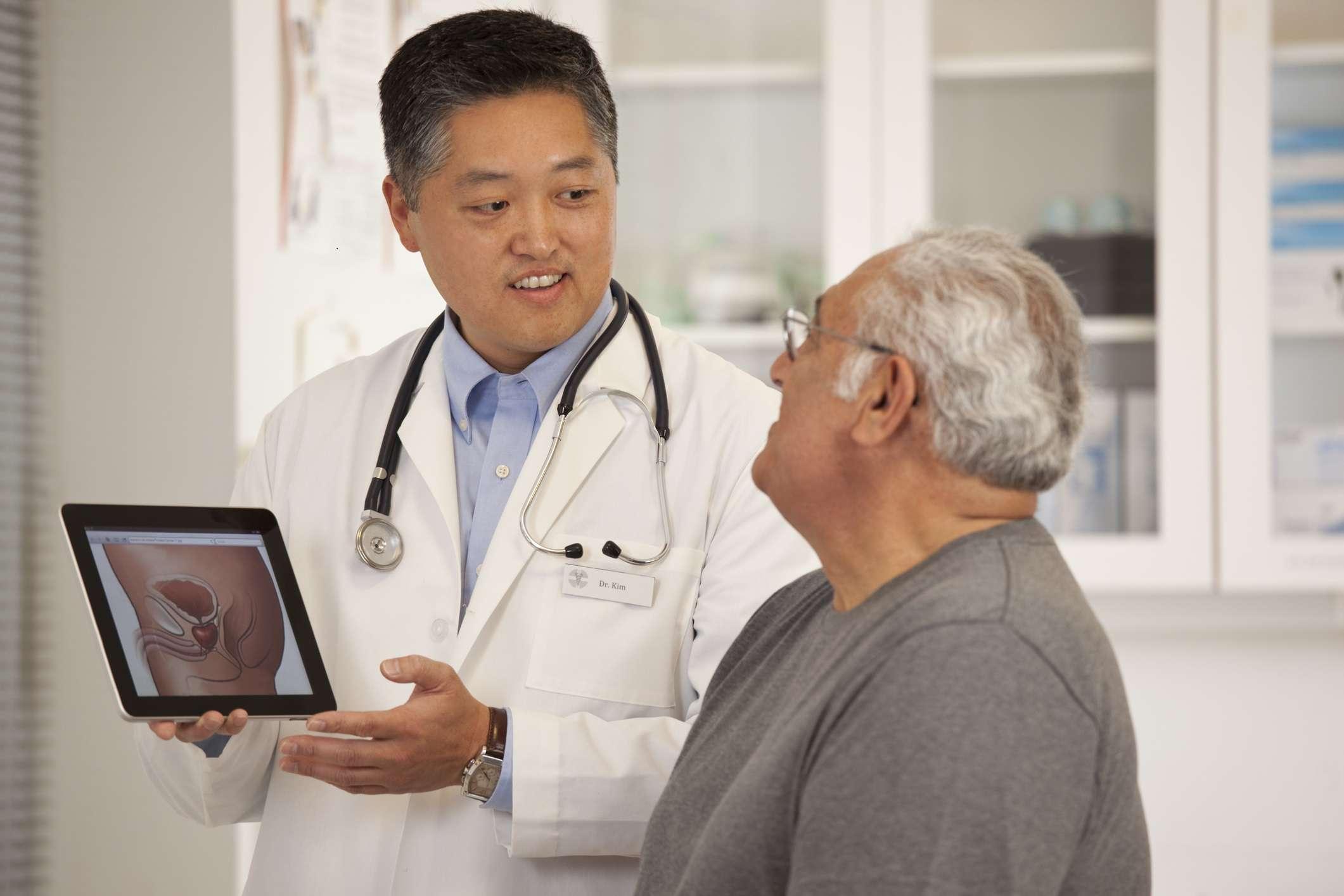 Doctor using digital tablet to talk to older adult man