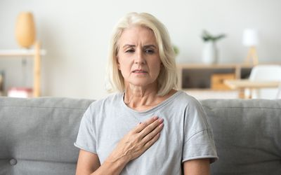 Upset stressed mature older woman feeling heartache touching chest