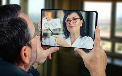 Telemedicine eye doctor shows an image to a male patient.