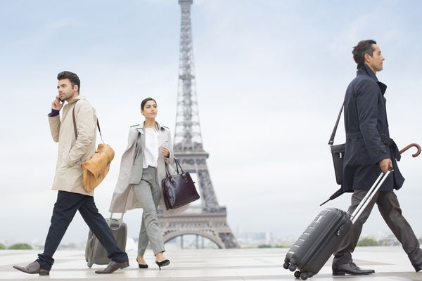 Three people travelling with cases