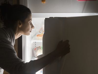 Woman looking in fridge for food