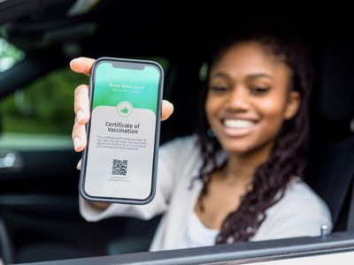 A young Black woman in a car holding up her phone with has a