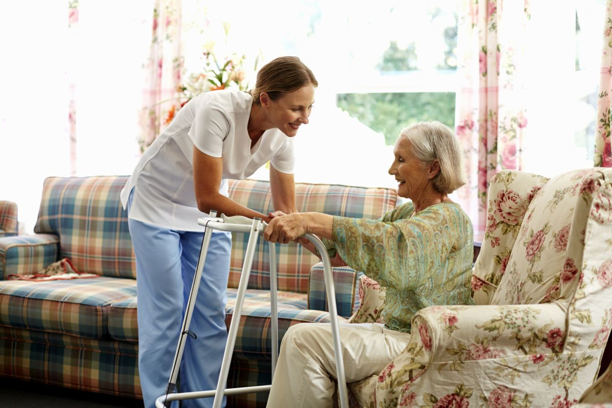 Physical therapist helping senior woman rising from a chair.