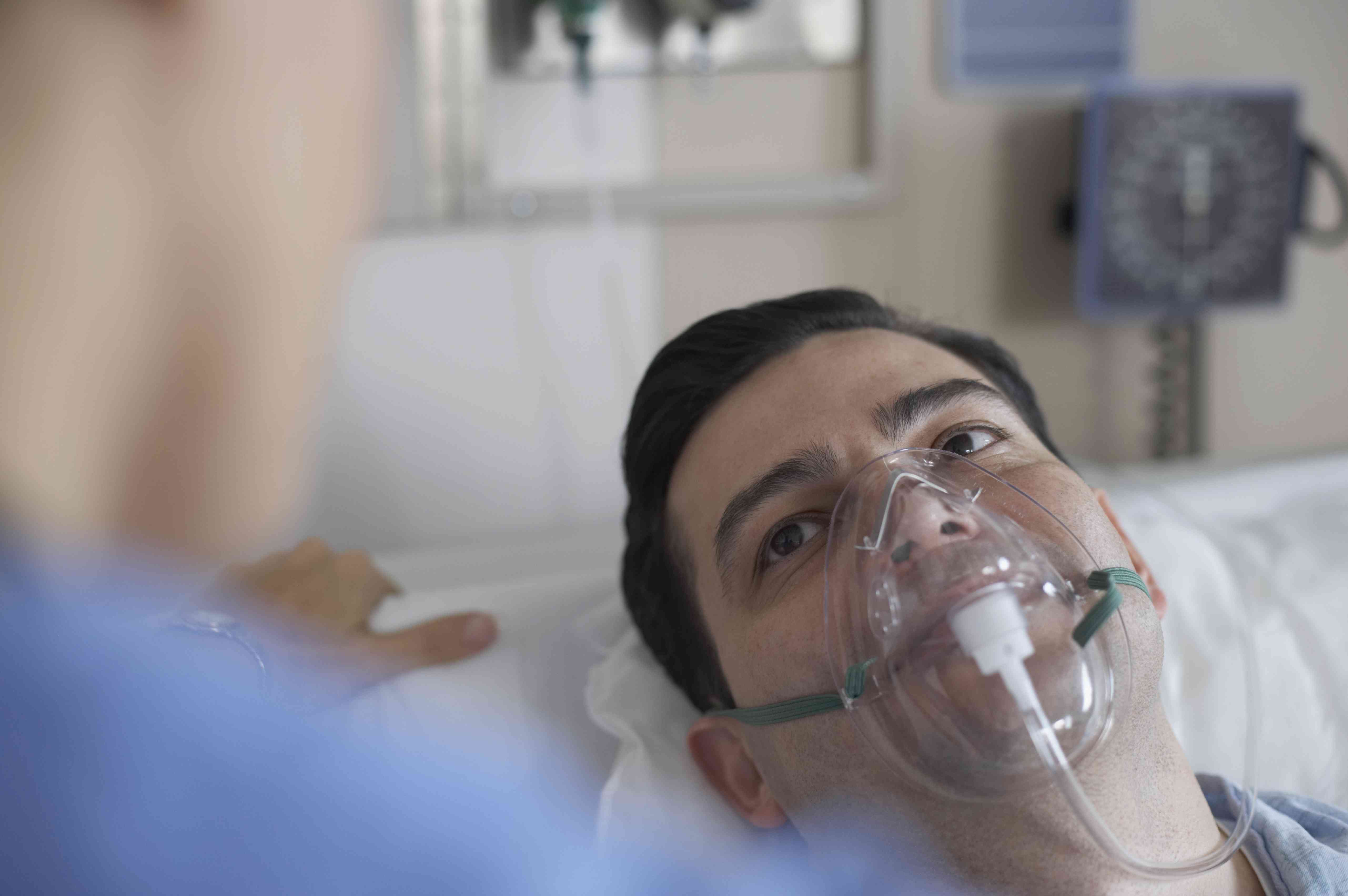 A man wearing an oxygen mask in the hospital