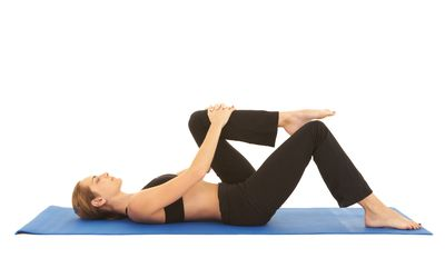 A woman lies in the supine position and stretches one knee to her chest.