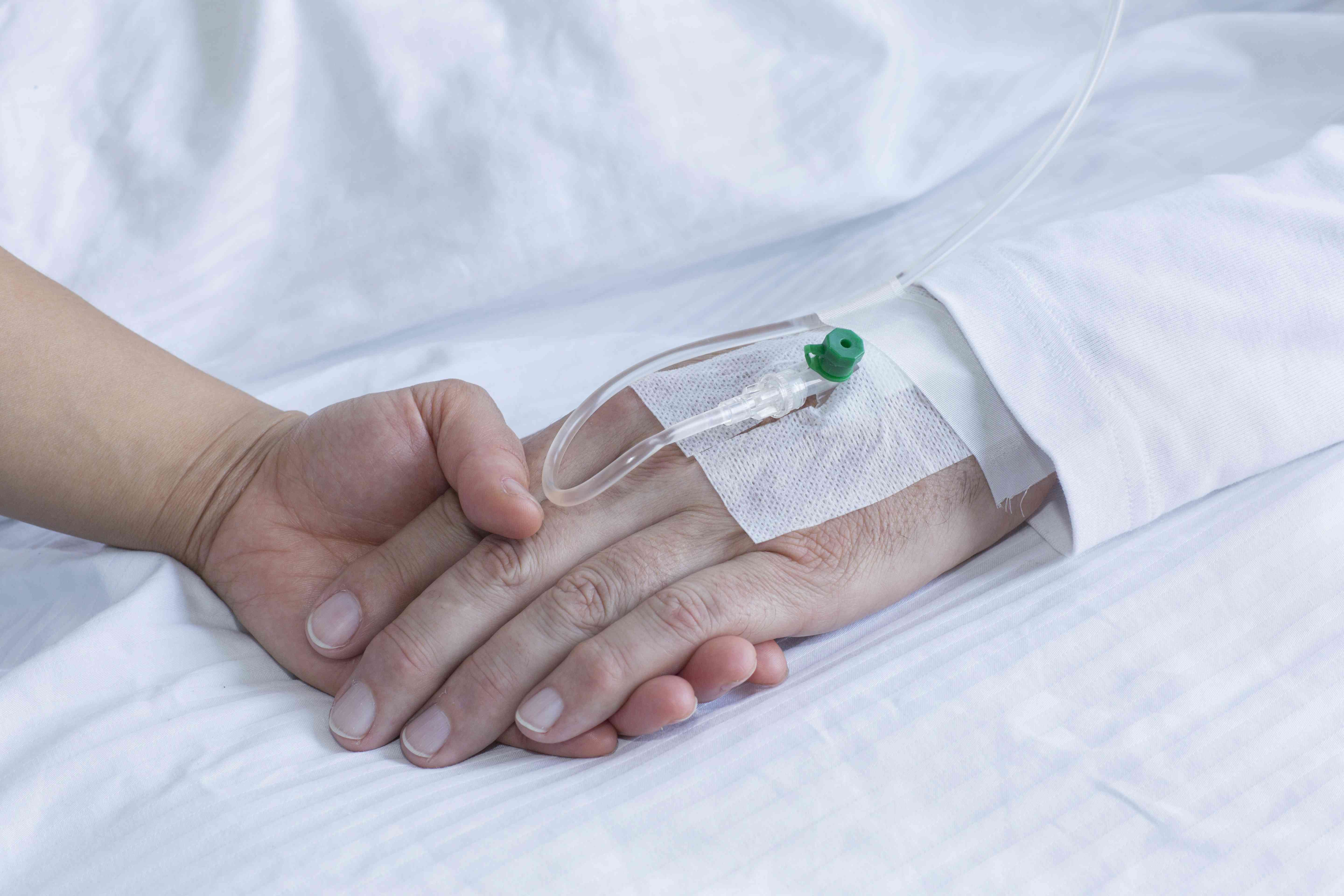 Woman holding hand of man in hospital, close up