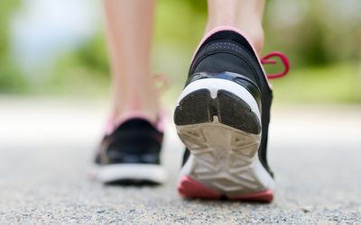 Closeup of a woman's heel while she's walking in running shoes