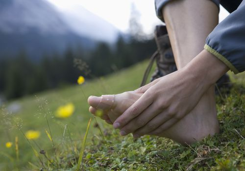 Close-up of woman with band aid on toe after hiking