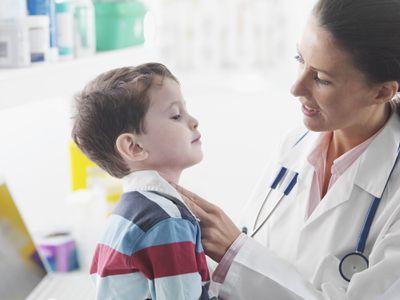 Doctor examining a young boy